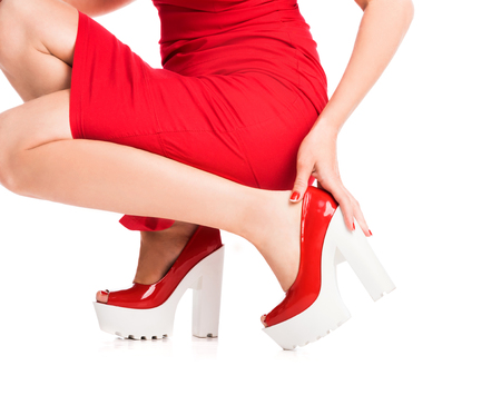 girl squats and fixes her red footwear