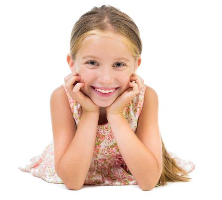 girl lying: portrait of smiling little girl lying on the floor isolated on white background