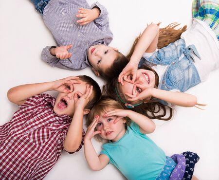 imitating: children lying on the floor with hands imitating glasses isolated on white background
