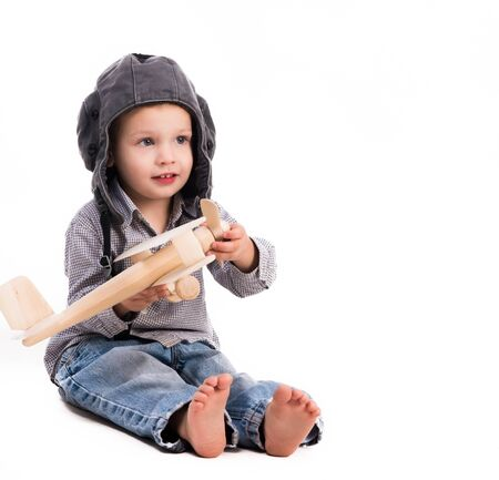 toy plane: little boy with pilot hat playing toy plane isolated on white background Stock Photo