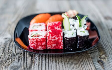 sushi plate: assorted Japanese sushi on a plate with chopsticks on wooden table