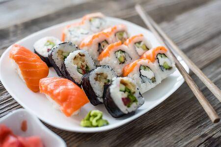 comida japonesa: diversos sushi japonés en la placa blanca con los palillos en el fondo de madera