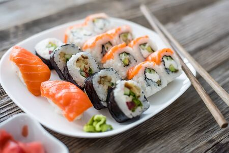 japanese food: various Japanese sushi on white plate with chopsticks on wooden background Stock Photo