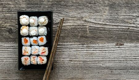 sushi: assorted sushi on black plate with chopsticks on wooden background