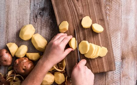 protein crops: hands cutting potato on wooden board