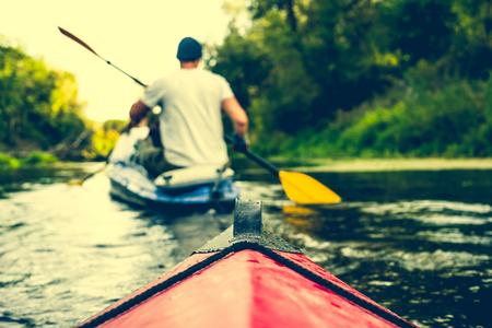 nariz: la nariz de la canoa flotando detrás remero en un río Foto de archivo