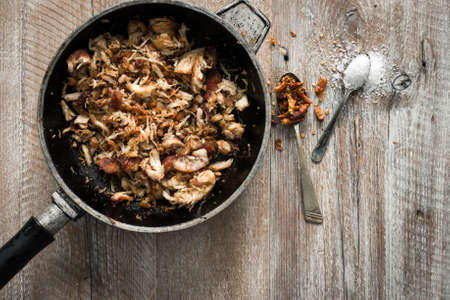 pan: stir-fried meat in pan on wooden table with spices Stock Photo