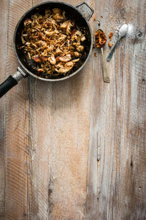 text space: fried meat in pan on wooden table with text space