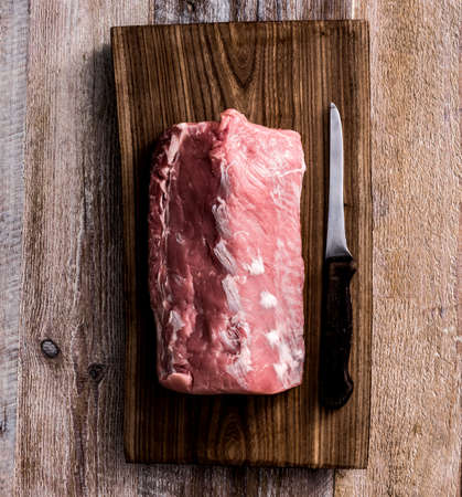raw beef: big piece of raw meat on cutting board Stock Photo