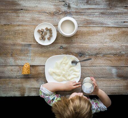 semolina: child near table having a meal with semolina Stock Photo