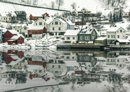 fjords: wooden houses on the banks of the Norwegian fjord, beautiful mountain landscape in winter