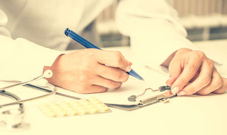 medical people: doctor writing a prescription at the workplace with pills and stethoscope