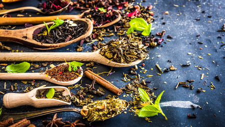 green and black: Virious kinds of tea in wooden spoons on black table