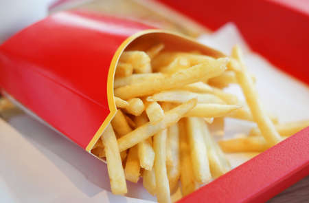 red food: golden crunchy french fries in red carton pack on a tray