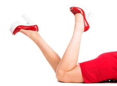 tacones rojos: hermosas piernas de la mujer en zapatos rojos con los pies en alto