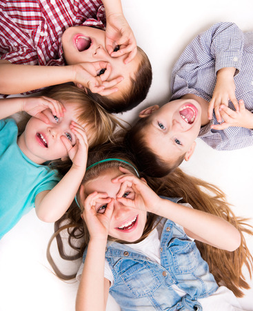 children background: children lying on the floor with hands imitating glasses Stock Photo