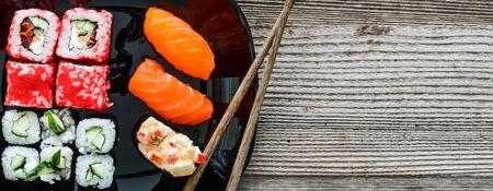 sushi en un plato con los palillos sobre fondo de madera