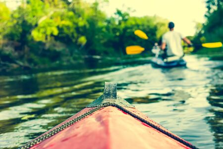 canoeing: nose of canoe floating behind rower on a river Stock Photo