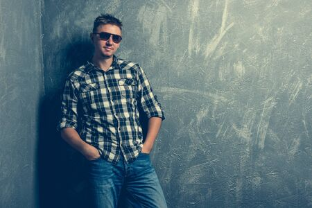 casual men: portrait of the man in sunglasses and plaid shirt