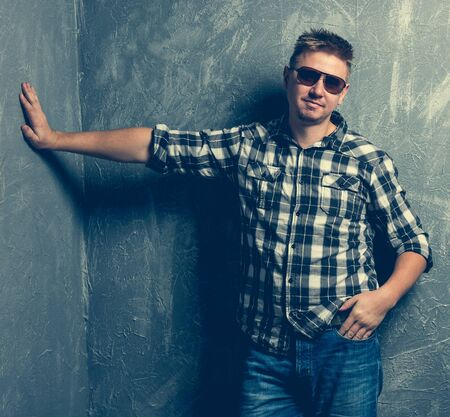 man shirt: man with his hand rest against the wall on grey background Stock Photo