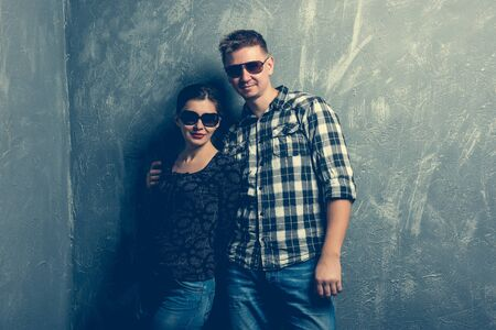 casual fashion: couple with sunglasses on grey background Stock Photo