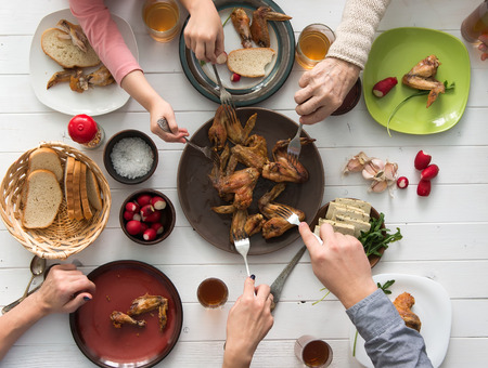 family having roasted chicken wings for dinner top view. Stock Photo