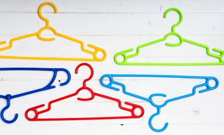 hangers: colourful clothes hangers on white wooden background