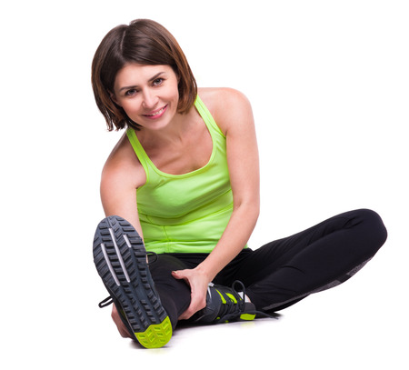 reaching out: sport girl stretching on the floor reaching out a foot with hand isolated on white background