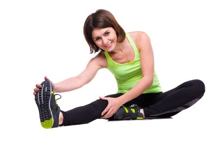 reaching out: sport woman stretching on the floor reaching out a foot with hand isolated on white background Stock Photo