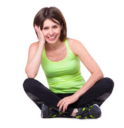 sports clothing: sport girl sitting on the floor with her legs crossed and resting isolated on white background