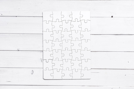 completed: white completed puzzle isolated on white wooden table