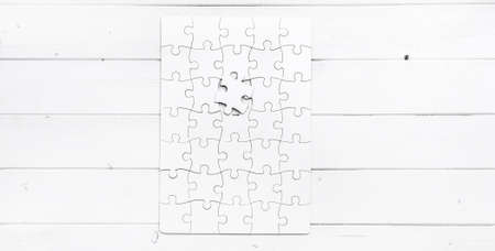 undone: white completed puzzle with one undone piece on white wooden table
