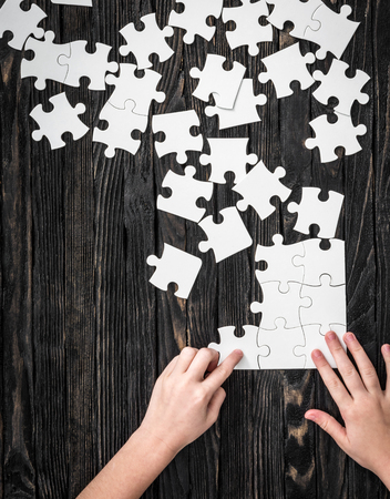 jigsaw puzzle pieces: hands starting to collect puzzle pieces on dark wooden table Stock Photo