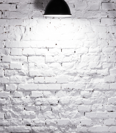 texture of brick whitewashed wall illuminated with lamp on top Banco de Imagens