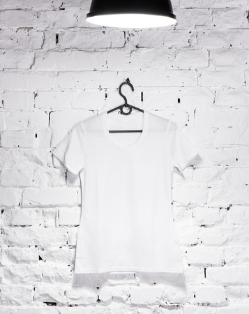 texture of brick whitewashed wall illuminated with lamp on top and a hanger with white woman shirt Foto de archivo