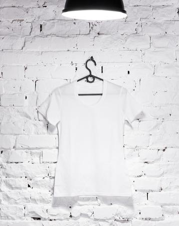 camisa: textura de la pared de ladrillo encalado ilumina con la lámpara en la parte superior y una percha con camisa blanca Mujer