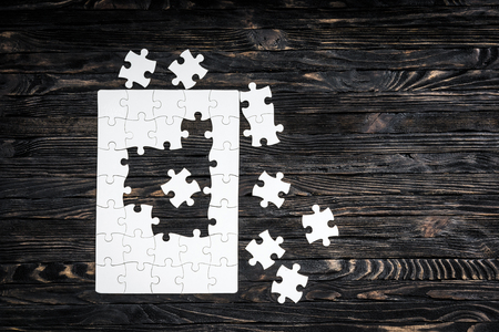 uncompleted: started puzzle with uncompleted center and pieces on dark wooden background Stock Photo
