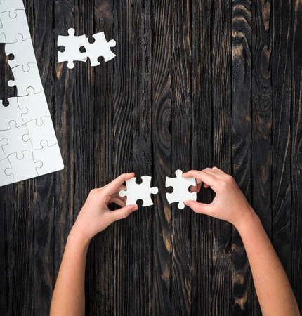uncompleted: hands holding pieces of white puzzle on dark wooden table with uncompleted puzzle