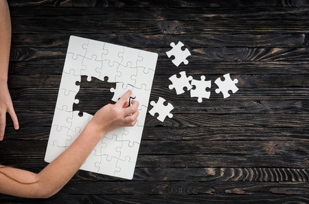 jigsaw puzzle pieces: hands with puzzle pieces on dark wooden table