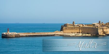 horison: postcard with lighthouse in Valletta port of Malta on misty sea background with a ship Stock Photo