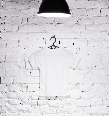 shirt hanger: texture of brick whitewashed wall illuminated with lamp on top and a hanger with white t-shirt