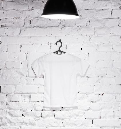 textuur van bakstenen witgekalkte muur verlicht met lamp aan de bovenkant en een hanger met wit t-shirt Stockfoto
