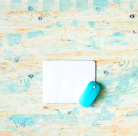 mousepad: white pad with blue mouse on colorful wooden background Stock Photo