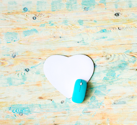 white heart: white heart shaped pad with blue mouse on colorful wooden background