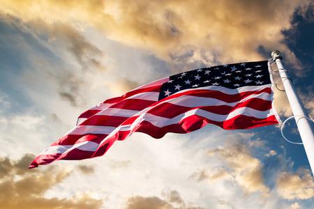 julio: bandera americana ondeando cielo azul Foto de archivo