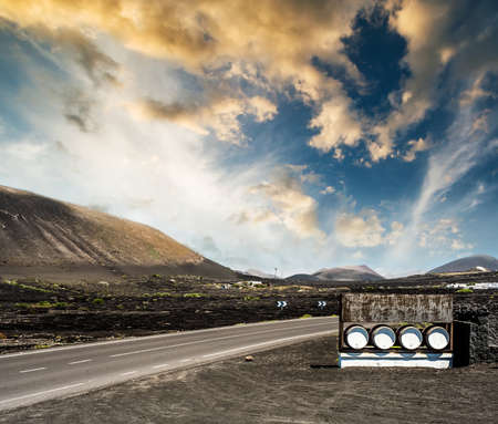 wine road: road and restaurant advertisement casks near mountains against sunset sky in Lanzarote, Canary Islands, Spain Stock Photo