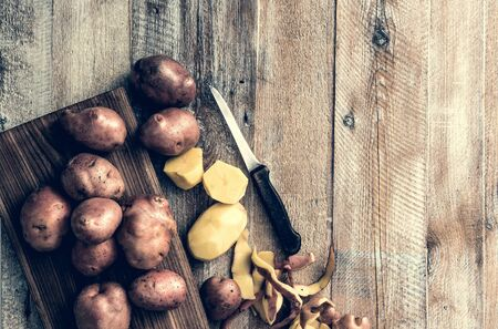 papas: la patata pelada y cortada en mesa de madera
