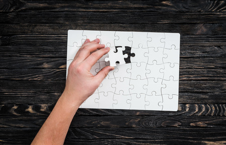 hand completing wthite puzzle with the last piece on dark wooden background Stock Photo