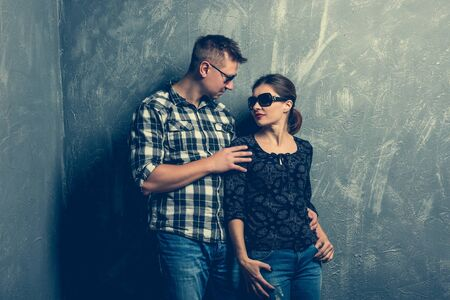 facing each other: portrait of couple facing each other on grey background Stock Photo