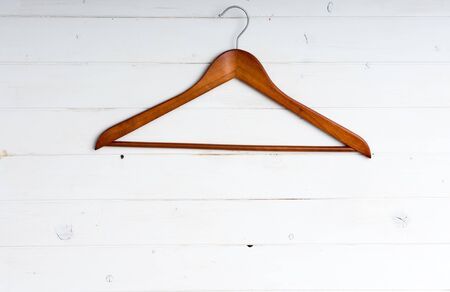 clotheshanger: wooden clothes hanger on white wooden background Stock Photo